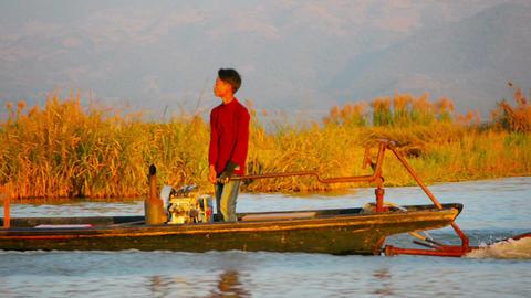 INLE LAKE. MYANMAR - CIRCA JAN 2014: Burmese teenager steers the boat with a mot Footage