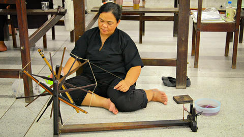 BANG PA-IN. THAILAND - CIRCA NOV 2013: Local artisan spinning thread by hand for Live Action