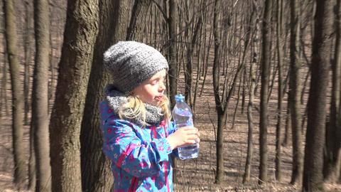 Little girl drinks water from a bottle. 4K UltraHD, UHD Footage