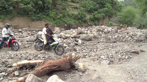 Motorbikes Cross Flood Ravaged Road stock footage