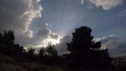 Moving clouds with sunbeams between forest and city Footage