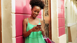 African American Girl Shopping And Text Messaging On Phone Footage