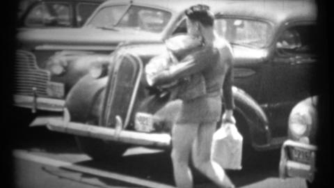 (1940's 8mm Vintage) Man Carrying Packages Across Parked Cars Footage