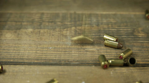 9mm bullet casings falling onto wooden floor Acción en vivo