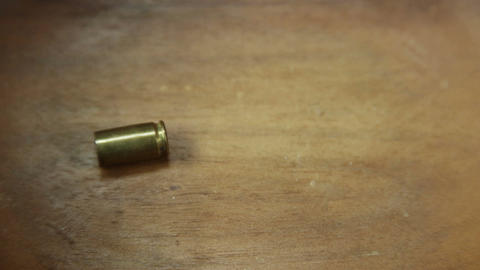 Bullet shell dropped onto wooden floor 4 K UHD Acción en vivo