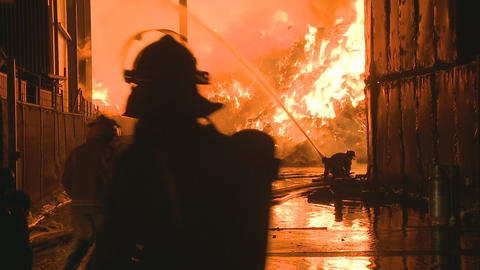 Fire crew fighting a large industrial blaze Stock Video Footage