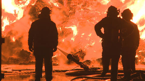 three firemen at a large industrial fire Stock Video Footage
