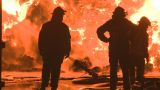 three firemen at a large industrial fire Footage