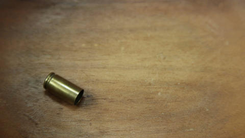 Single 9 mm bullet casing dropped onto wood 4 K UHD Archivo