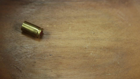 Single bullet cartridge falling and coming to rest on wooden floor 4 K UHD Footage
