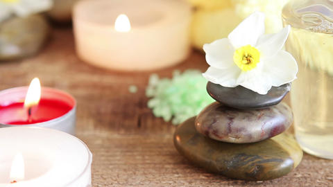 Spa still life containing bath salt , rocks , massage oil , candles and flowers Live Action
