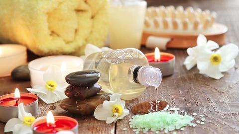 Spa still life of massage oil , towel , rocks and flowers 1 Footage