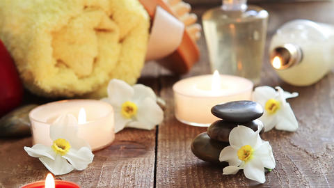 Spa still life of massage oil , towel , rocks and flowers Live Action