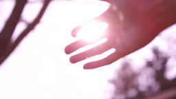 Sun's rays through fingers of female hand Footage