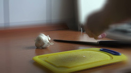 Chopping and peeling garlic with knife on cutting board, real time Footage