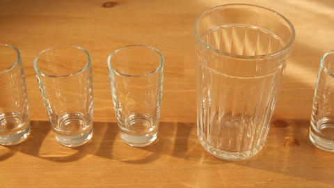 Hovering Over Small Glasses And A Big One stock footage