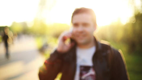 Man Calling On Mobile Phone At Sunset In Park. Blur. Out Of Focus. Smiling And L stock footage