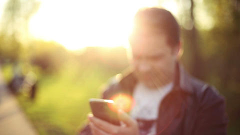 Man using app on Smart Phone at Sunset. Blur. Out of Focus. HD 1080 Footage