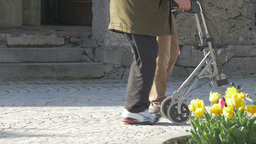 elderly man is walking with a walking frame Live Action