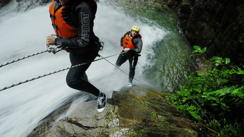 Real Time Action Shot Of Two Tourist Rappelling Trough Tall Waterfall stock footage