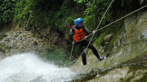 Adult women rappelling huge waterfall in Andes rainforest Footage