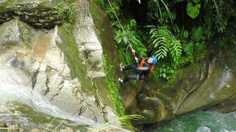 Adult adventurer women rappelling into waterfall Footage
