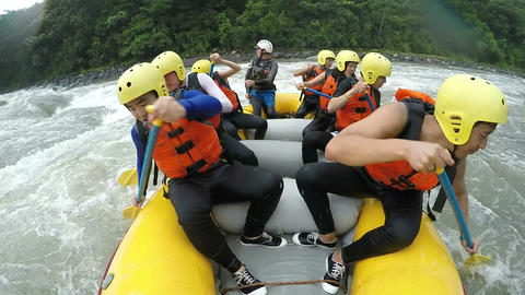 Group of eight Asiatic people white water rafting back paddling Footage