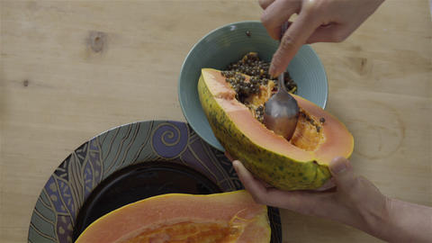 Scooping out the seeds from a Papaya 4K UHD Live Action