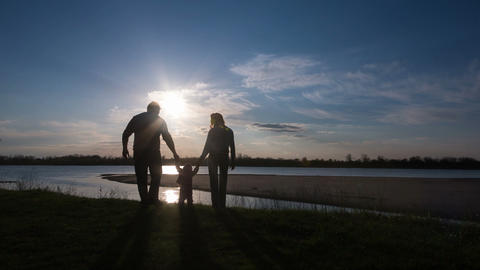 Happy Family Walking on River Bank Silhouettes Sunset Footage