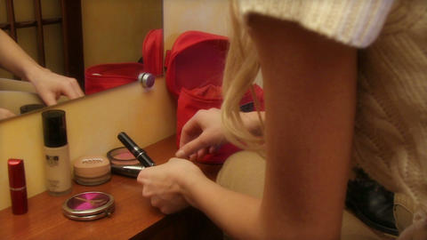 Beautiful young girl applying cosmetic in front of mirror Footage