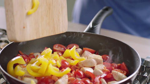 Adding vegetables into pan with chicken Footage