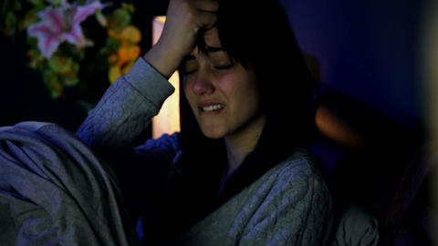 Sad desperate woman in bed crying alone closeup Footage