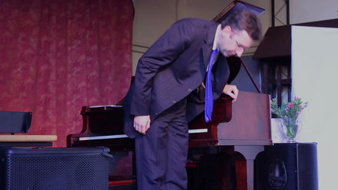 Male finish playing the piano and bowing to the audience Live Action
