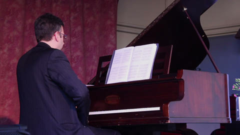 Male plays piano with one hand and both hands Live Action