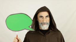 Friar holding green speech balloon serious Footage