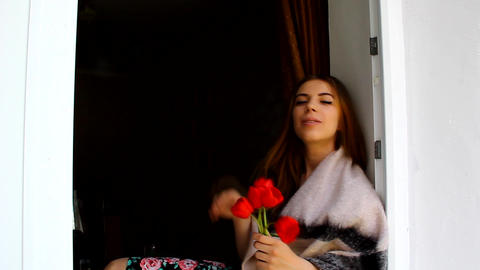 A young girl with tulips sitting on the windowsill, and sends kisses Footage