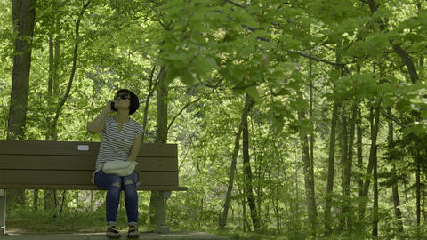 Asian woman talking on cellphone as she sits on park bench. 4K UHD Footage