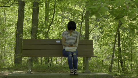 Asian Woman Texting While Sitting On Park Bench. 4K UHD stock footage