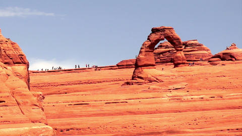 People move around Delicate Arch exploring the desert landscape Footage