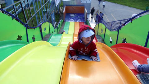 Small children ride a sliding board Live Action
