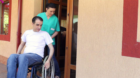 Nurse With Young Man In Wheelchair Going Fora Walk stock footage