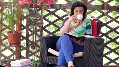 Young woman reading book while drinking coffee Footage