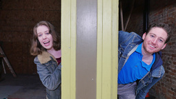 A young man and woman playfully poke their heads out from behind a post Footage