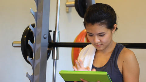 Fitness woman using tablet in the fitness club Live Action