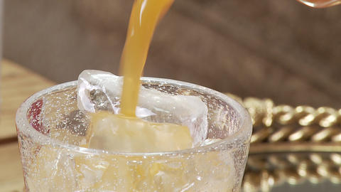 Close Up- Juice Pours Into Glass Of Ice- Slow Motion stock footage