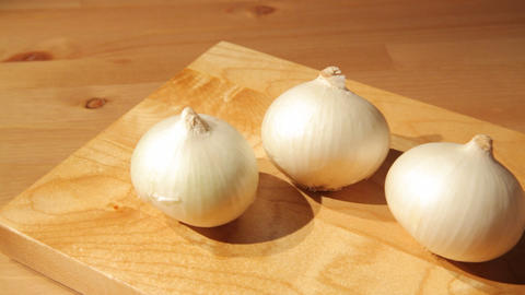 Three onions on a wooden board Footage