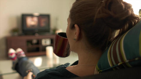 Woman Relax On Sofa Watching Film On TV With Remote Footage