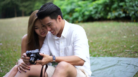 Asian couple looking at own camera Footage