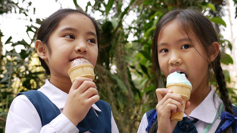 4K Video of little Asian girls enjoying ice cream together Footage