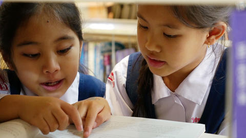 4K UHD : Little Asian students with uniform reading book in library together Footage